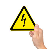 Isolated male hand holding sign of danger high voltage symbol — Stock Photo
