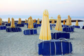 Closed umbrellas and sunbeds on a deserted beach — Stock Photo