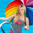 Beautiful girl by the pool with colored umbrella — Stock Photo #21727983