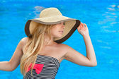 Beautiful girl in the hat at the pool — Stock Photo