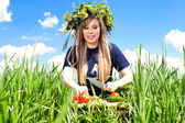 Beautiful girl in a field of flowers cut vegetables — Stock Photo