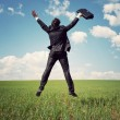 Businessman in suit jumping in field and holding the bag — Foto Stock