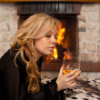 Beautiful girl by the fireplace — Stock Photo
