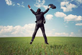 Businessman in suit jumping in field and holding the bag — Stock Photo