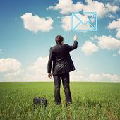 Hombre de negocios de pie en el campo y señala con un dedo en el correo — Foto de Stock