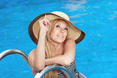 Beautiful girl in the hat in the pool — Stock Photo