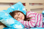 Beautiful little girl sleep in bed under a blue blanket — Stock Photo