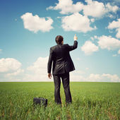 Businessman standing in the field and points a finger at something — Stock Photo