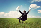 Businessman sitting on a chair in a field and holding documents — Stock Photo