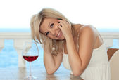 Beautiful girl talking on the phone in a cafe and drink wine — Stock Photo
