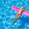 Sexy girl floating on a mattress in the sea or swimming pool — Stock Photo