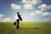Empresário de fato andando sobre um campo verde espaçoso com um b — Foto Stock
