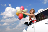 Portrait a girl in the car with colorful balloons — Stock Photo