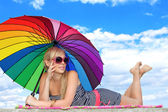 Glamorous girl in retro style by color umbrella on the beach — Stock Photo
