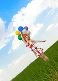 Pretty girl playing with balloons in a field on holiday — Stock Photo