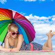 Glamorous girl in retro style by color umbrella on the beach — Stock Photo #22652343