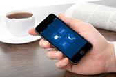 Mano di uomo d'affari che tiene un telefono con interfaccia su un schermo agai — Foto Stock