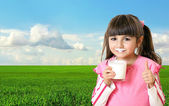 Beautiful girl holding a glass of milk in the background of gree — Stock Photo