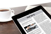 Tablet with business news on screen on a table at a businessman — Stock Photo