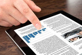 Male hand touching tablet with business news on screen — Stock Photo