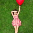 Beautiful girl lying on the grass and holding a red ball in the — Stockfoto