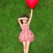 Beautiful girl lying on the grass and holding a red ball in the — Stock fotografie