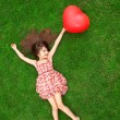 Beautiful girl lying on the grass and holding a red ball in the — Stock Photo #26683131
