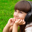 Beautiful little girl lying on green grass with headphones — Stock Photo