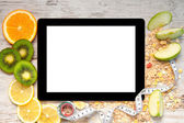 Tablet computer with fruit and a measuring tape for weight loss — Stock Photo