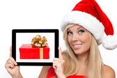 Girl in a red Christmas hat on New Year, holding tablet computer — Stock Photo