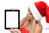 Girl in a red Christmas hat on New Year, holding tablet touch pa — Stock Photo