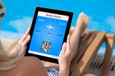 Girl lying on a deck chair by the pool and holding a tablet with — Stock Photo