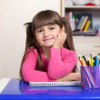 Little girl sitting in the children room at the table with color — Stock Photo