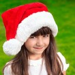 Portrait of a little girl in a Christmas hat on a background of  — Stock Photo