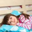 Little girl in pajamas sleep in bed under a blue blanket — Stock Photo