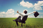 Businessman in a field with a blue sky sitting on an office chai — Foto de Stock