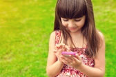 Beautiful girl holding a phone on a background of green grass — Stock Photo