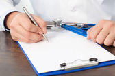 Doctor sitting at his desk with a stethoscope and writing something on a sheet — Stock Photo