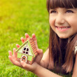 Portrait of a little girl with house in hand on a background of — Stock Photo