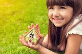 Portrét holčičky s domem v ruce na pozadí — Stock fotografie