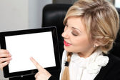 Beautiful woman in the office holding a tablet with isolated scr — Stock Photo