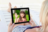 Woman in a bathing suit lying on a chaise lounge with a tablet a — Stock Photo