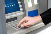 Man enters a PIN code and withdraws money from an ATM — Stock Photo