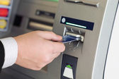 Male hand businessman inserts credit card into the ATM — Stock Photo