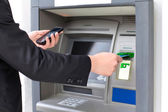 Businessman inserts a credit card into the ATM to withdraw money — Stock Photo