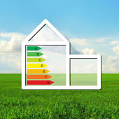 House with the sign of energy saving on a background of field — Stock Photo