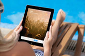 Girl lying on a sun lounger by the pool and holding iPad with Tw — Stock Photo