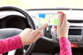 Female driver hand holding a phone with interface navigator on a — Stock Photo