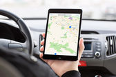 Man sitting in the car and holding a mini iPad with Apple Maps o — Stockfoto