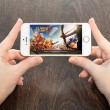 Постер, плакат: Female hands holding a white iPhone with Clash of clans on the s